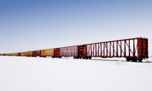 Train Hauling Industrial Bridging In Winter White Out