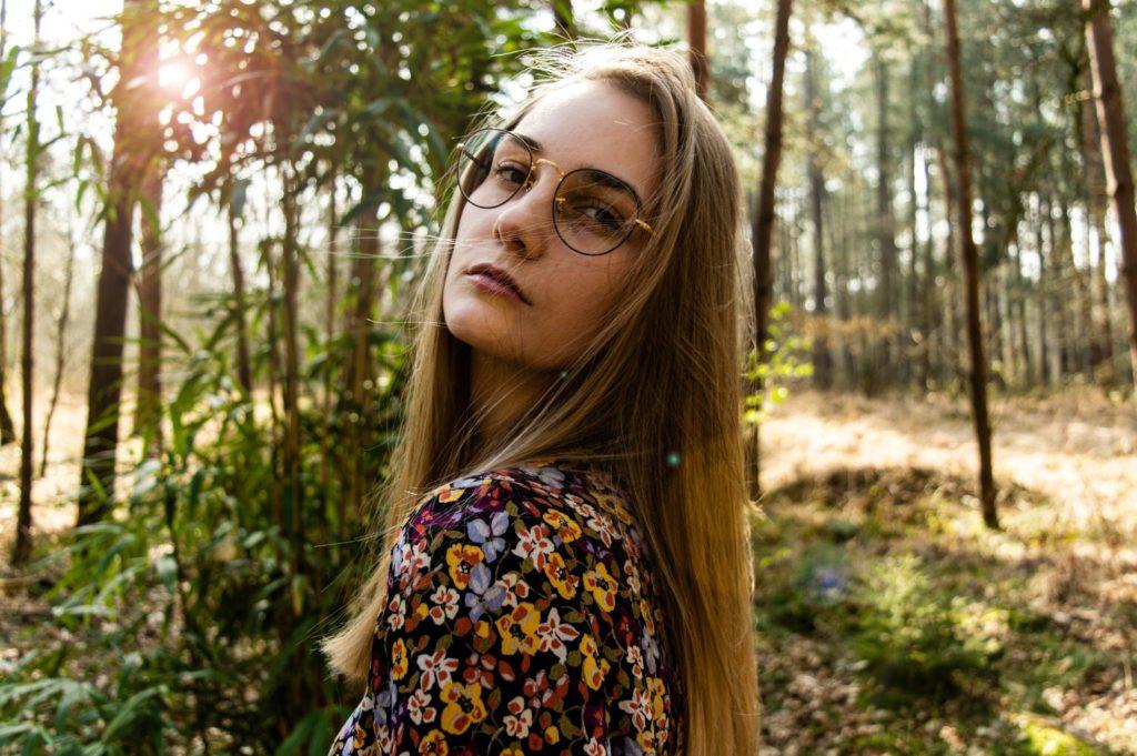 Kobieta w okularach na tle lasu